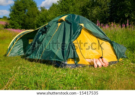 Three pairs foots stick out of tent - stock photo