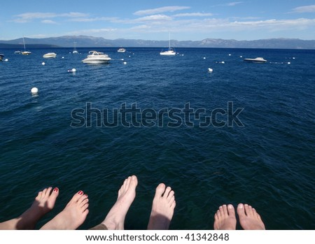 Three pairs of feet at the bottom of the frame with the blue of Lake Tahoe filling the rest. - stock photo