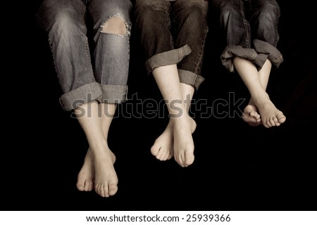 Three pairs of feet in jeans rolled up on a black background. One pair of jeans ripped at the knee's - stock photo