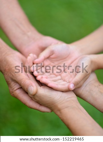 Three pairs of hands are held together. Care concept