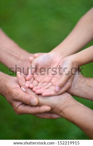Three pairs of hands are held together. Care concept - stock photo
