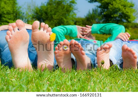 Three pairs of happy feet from mom and her two sons - stock photo