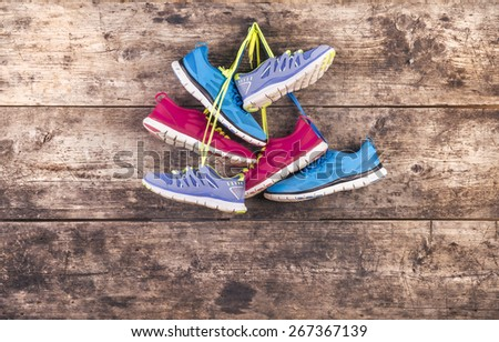 Three pairs of running shoes hang on a nail on a wooden fence background - stock photo