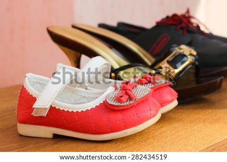 Three pairs of shoes: men, women and children. - stock photo