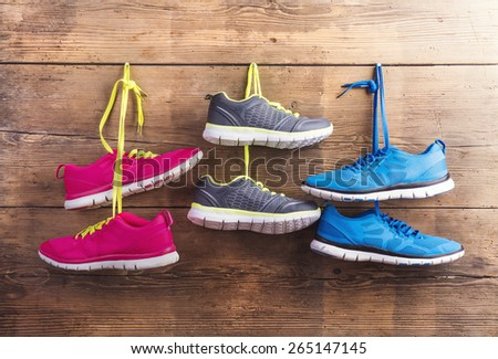 Three pairs of sneakers hang on a nail on a wooden fence background - stock photo