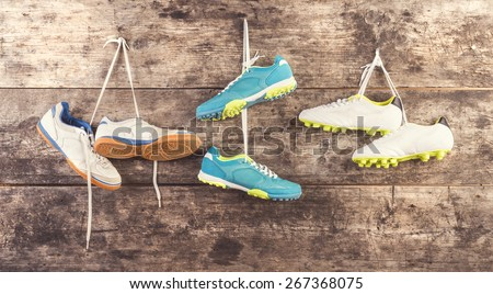 Three pairs of sports shoes hang on a nail on a wooden fence background - stock photo