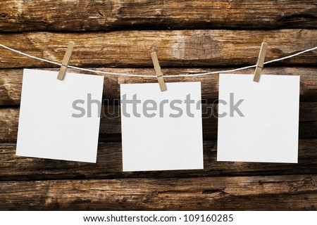 three  paper attach to rope with clothes pins on old wooden background - stock photo