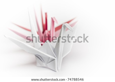 Three paper birds lining up on a white background, high-key and shallow depth of field - stock photo