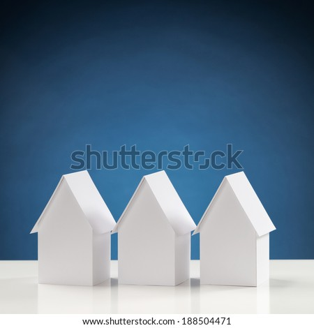 Three paper houses next to each other with a blue background behind them.