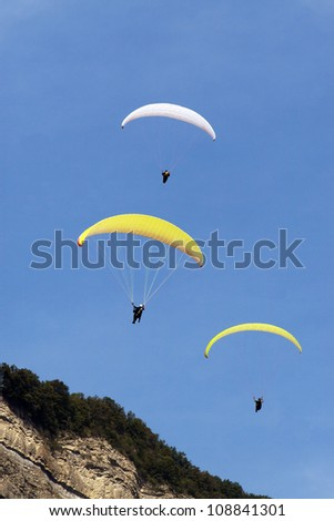 Three para gliders flying in formation over a mountain top against a clear blue sky. - stock photo