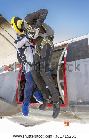 Three parachutists jumping out of an airplane in free style. - stock photo