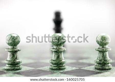 Three pawns in a raw standing in front of king shape. - stock photo