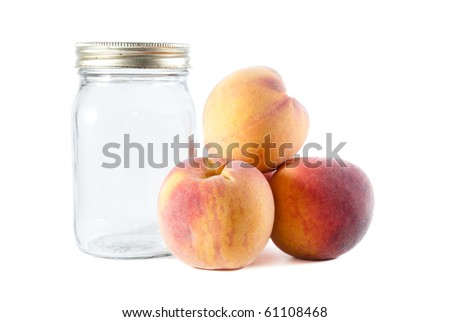 Three peaches piled beside a glass preservative jar on a white isolated background. - stock photo