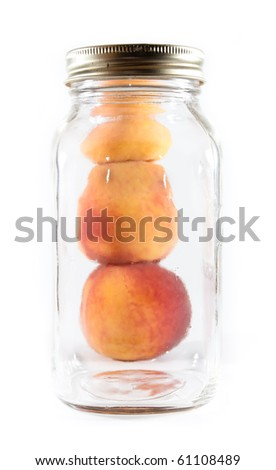 Three peaches stacked beside a glass preservative jar on a white isolated background. - stock photo