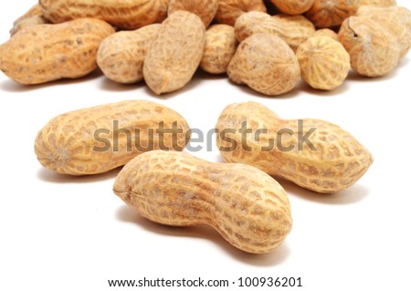 Three Peanuts Isolated on White With Many More In the Background - stock photo
