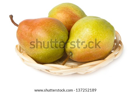 Three pears in wicker basket isolated on white background - stock photo