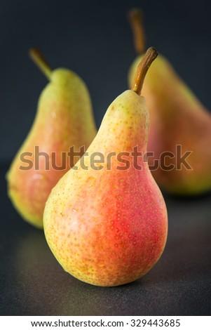 Three pears on dark background - stock photo