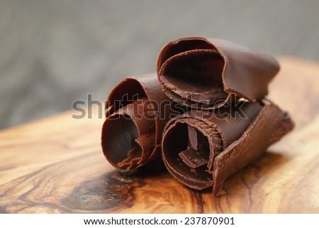 three peeled chocolate curls on olive wood board, closeup photo - stock photo