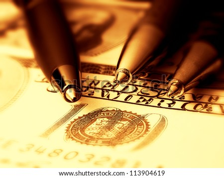 Three pens on a dollar banknote. Gold tone. - stock photo