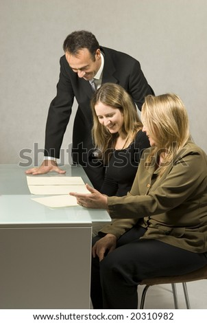 Three people are in a business meeting.  They are smiling and looking at some pieces of paper on the table.  The women are sitting and the man is standing.  Vertically framed shot.