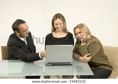 Three people are in a business meeting together.  They are smiling and looking at the screen of the laptop in front of the younger woman.  Horizontally framed shot. - stock photo