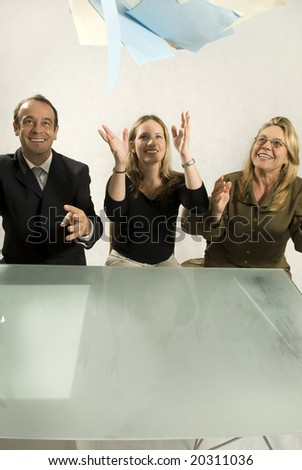 Three people are in an office in a meeting.  They are smiling and throwing papers in the air in success.  Vertically framed shot. - stock photo