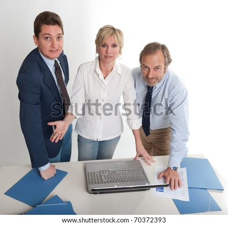 Three people around a laptop looking at the camera