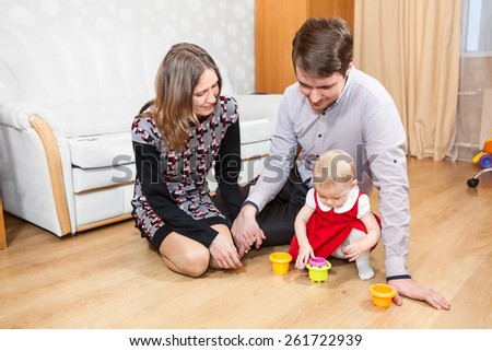 Three people Caucasian family playing on floor in room - stock photo