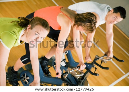 Three people cycling in a gym or fitness club, dressed in colorful clothes; focus on the girl in green looking into the camera