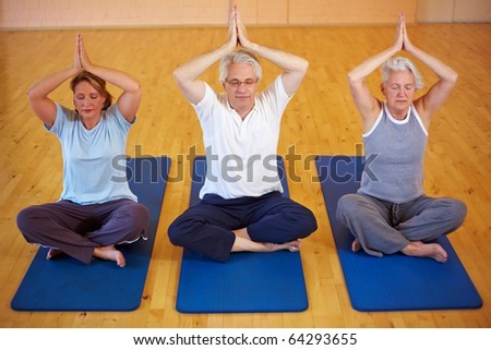 Three people doing Yoga in a gym - stock photo