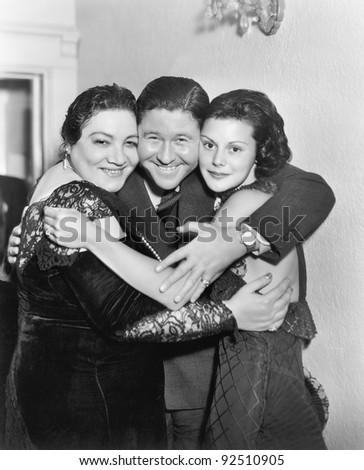 Three people embracing and laughing - stock photo