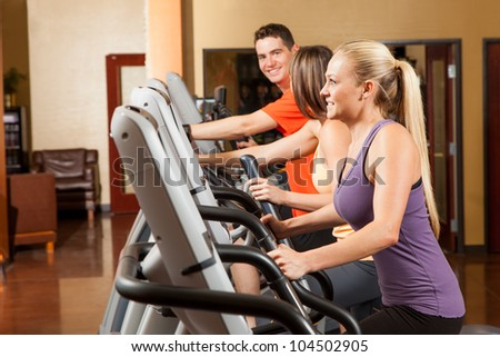 Three People Exercising on Elliptical Trainers at Fitness Center - stock photo