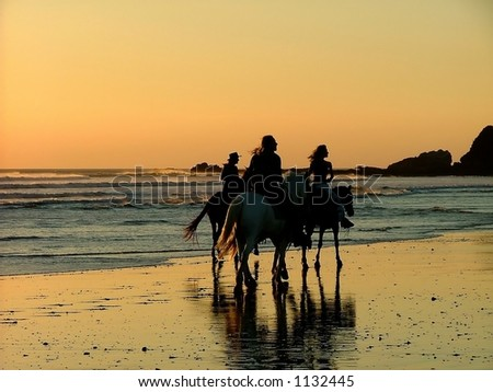 three people horse riding at sunset on beach - stock photo