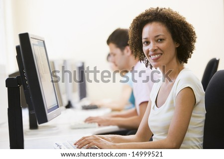 Three people in computer room typing and smiling - stock photo
