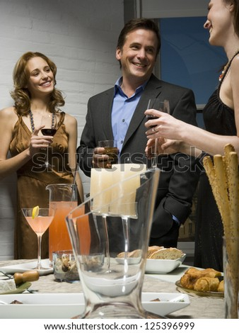 Three people in elegant dress talking at a party