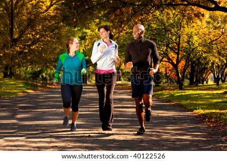 Three people jogging in the park on a beautiful fall day