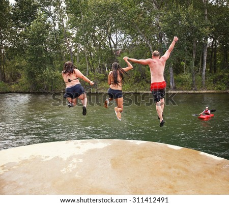 three people jumping off a concrete structure into a river toned with a retro vintage instagram filter effect app or action - stock photo