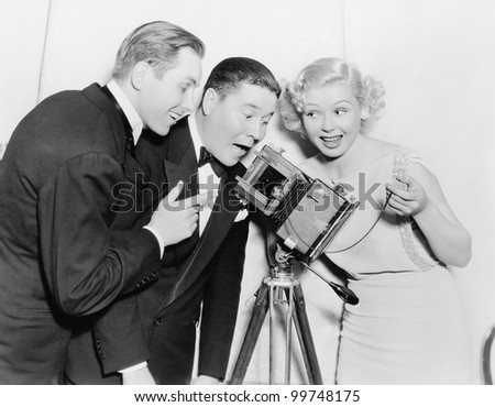 Three people looking through a camera and laughing - stock photo