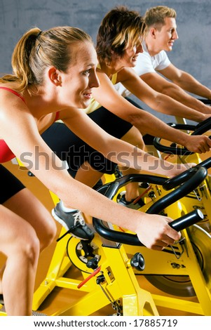 Three people on bicycles in a gym or fitness club for a workout - stock photo