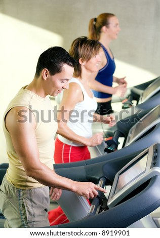 Three people on the treadmill in a gym, one choosing the program on the machine
