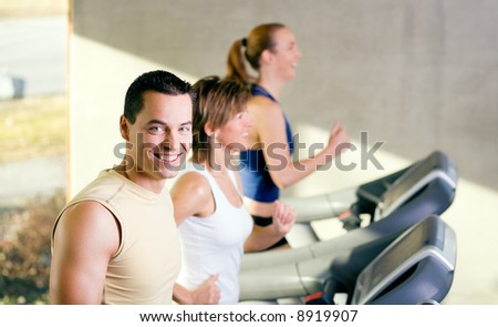 Three people on the treadmill in a gym, young man I front smiling