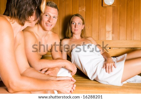 Three people (one male, two female) relaxing in a sauna - stock photo