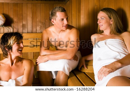 Three people (one male, two female) relaxing in a sauna, doing a lot for their health but also having fun with it - stock photo