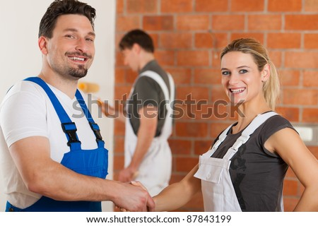 Three people - one woman and two men - renovating an apartment; the couple in front are shaking hands - stock photo