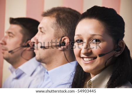Three people sales representative working in office,focus on woman smiling,men standing in profile with headset - stock photo