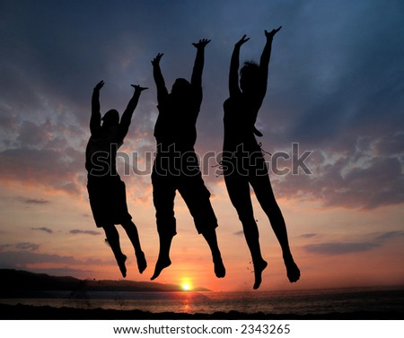Three people silhouettes jumping on the beach - stock photo