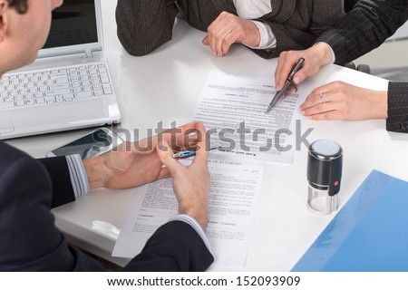Three people sitting at a table signing documents, hands close-up - stock photo