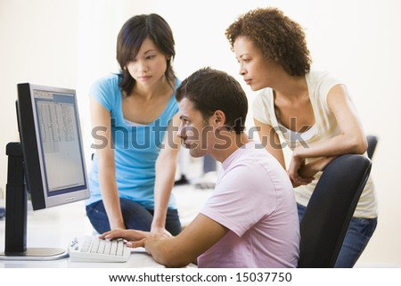 Three people sitting in computer room looking at monitor - stock photo