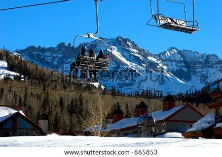 three people sitting on chairlift with mountain vista, snowcovered roofs and passing gondola car