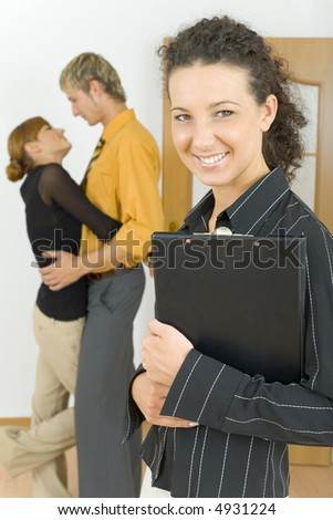 Three people standing in flat. One couple is hugging, other woman is standing alone and looking at camera. Everyone smiling - stock photo